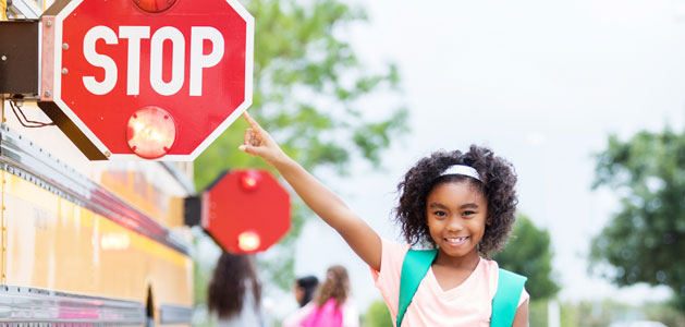 image of student pointing out stop sign on school bus