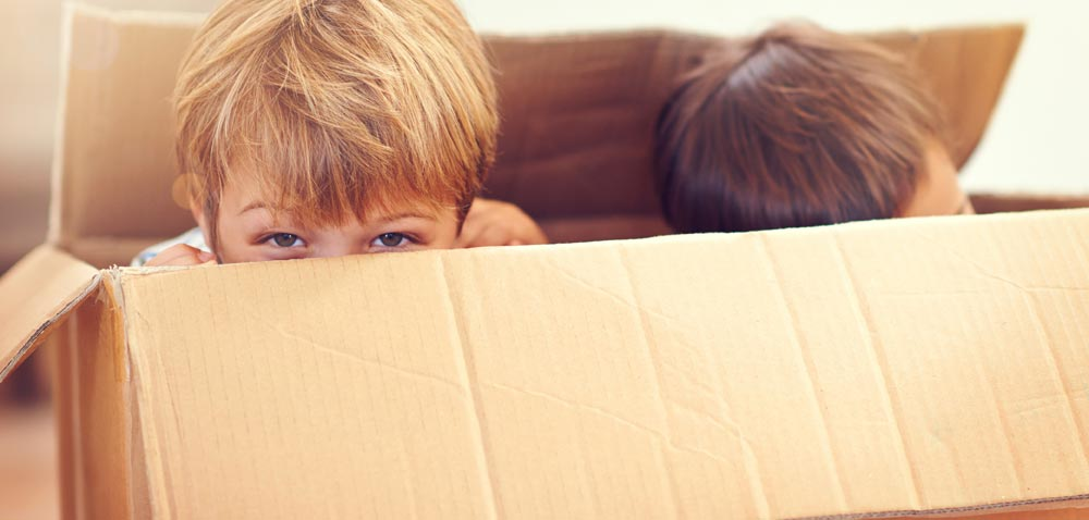 Two children playing in a box